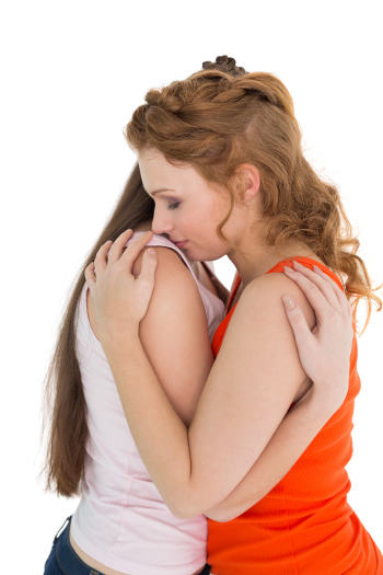 A lesbian couple hugging, consoling each other